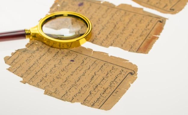 ライトと虫眼鏡のあるテーブルにアラビア語の原稿が書かれた本のページ
