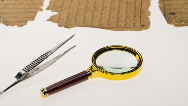 Book pages with an arabic manuscript on a table with a light and a magnifying glass