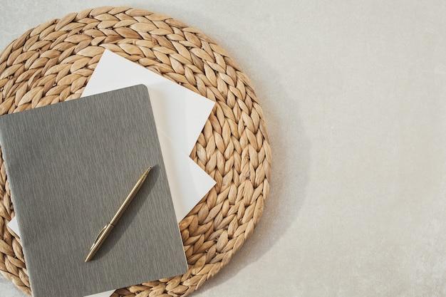 중립 베이지 색 콘크리트 표면에 책, 펜, 짚 스탠드