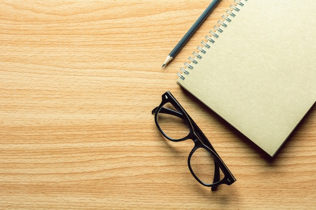 Book, pencil and a glasses on wooden desk