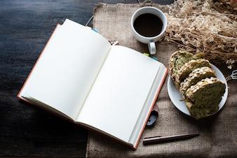 黒いコーヒーカップと全粒小麦のパンの横に置かれた本、