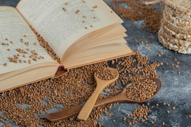 Book, raw buckwheat and crispbread on marble surface