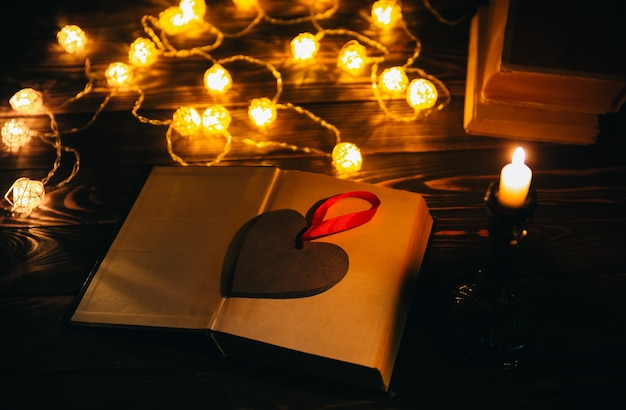Book reading for cosy evening. holidays mood photo with christmas lights. wooden heart and candle. hygge concept. perfect autumn flat lay.