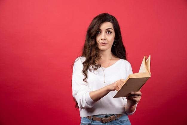 빨간색 배경에 서있는 여자를 읽고 책. 고품질 사진