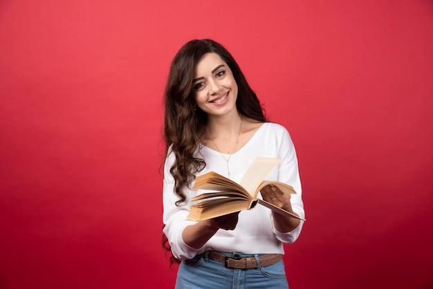 Libro lettura donna in piedi su uno sfondo rosso. foto di alta qualità