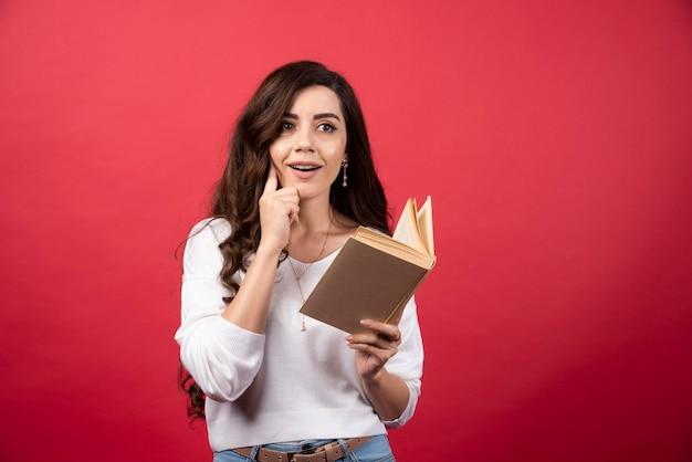 Prenota lettura donna pensando su uno sfondo rosso. foto di alta qualità