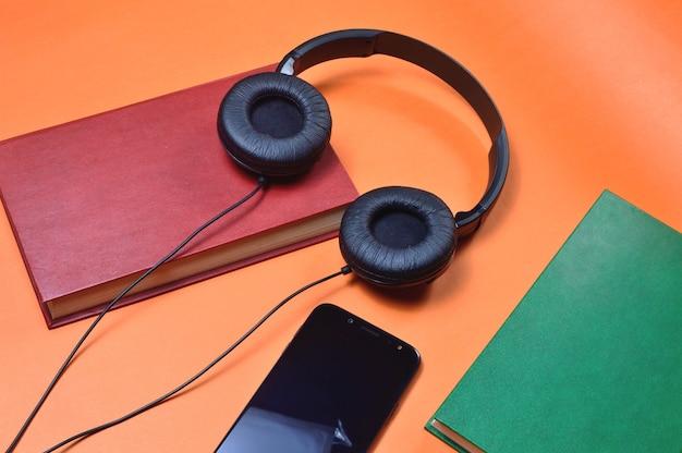 Книга, смартфон, наушники на оранжевом столе. аудиокнига. хобби. свободное время. отдых. литература.