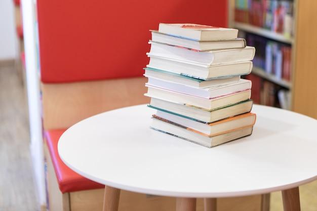 Book stack on white desk and blurred bookshelf