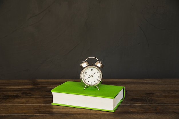 Book on table with alarm clocks