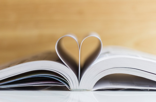 Book on the table with pages folded into a heart shape