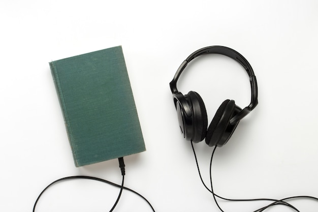 青いカバーと白い背景に黒いヘッドフォンが付いている本。オーディオブックと遠隔学習の概念。フラット横たわっていた、トップビュー