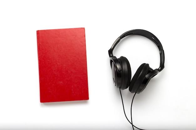 赤いカバーと白い背景に黒いヘッドフォンが付いている本。オーディオブックと遠隔学習の概念。フラット横たわっていた、トップビュー