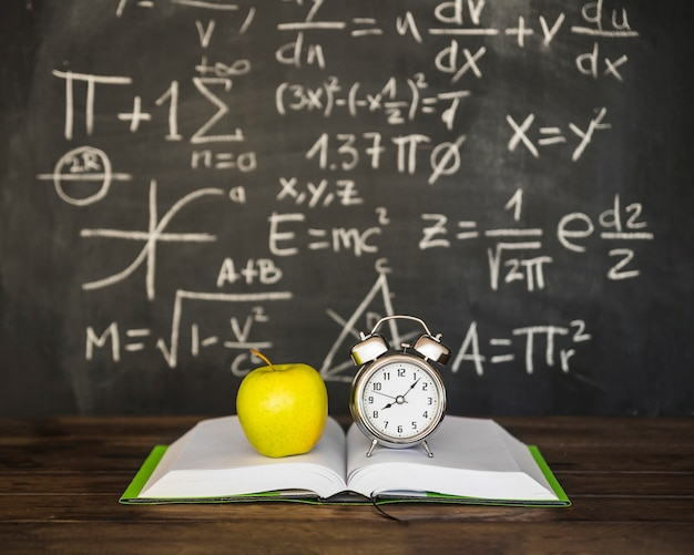 Book with apple and alarm clocks near blackboard