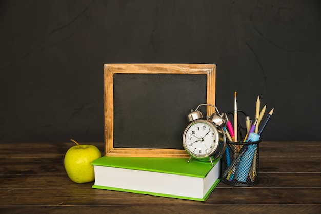 Book with blackboard and alarm clocks on table with stationery