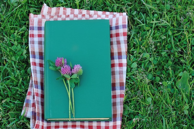 Book with a blank cover on the grass, top view. outdoor reading, summer vacation.