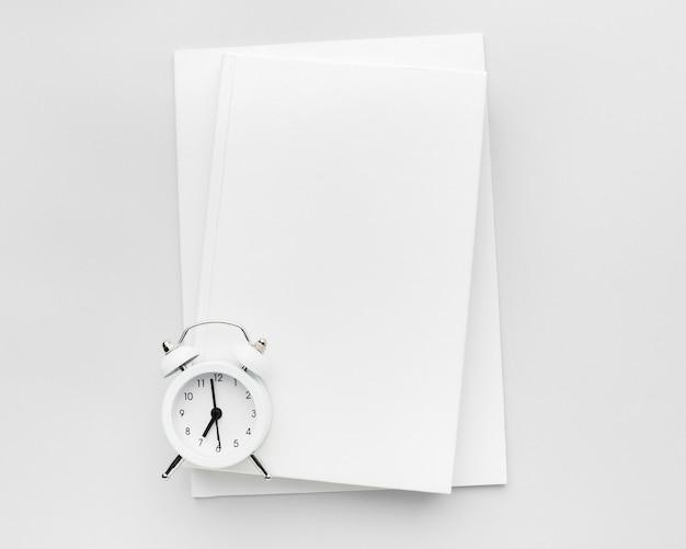 テーブルの上の時計が付いている本