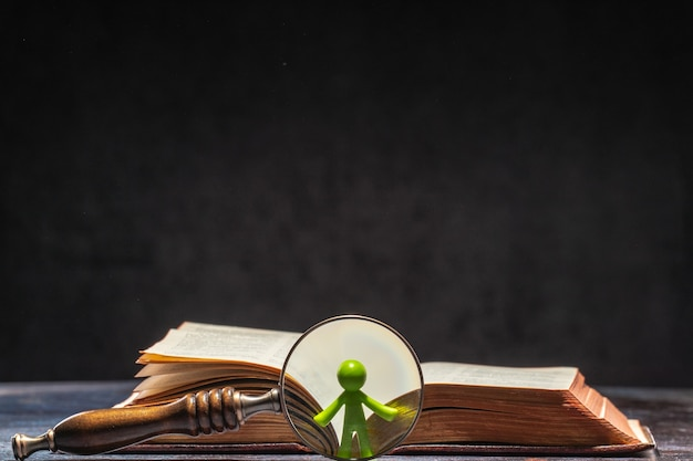 A book with a figure of a man visible through a magnifying glass. knowledge and education concept.