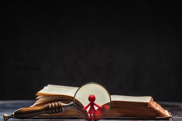 A book with a figure of a women visible through a magnifying glass. knowledge and education concept.