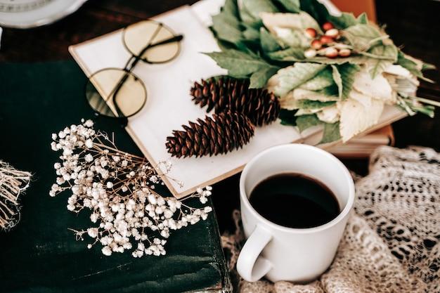 ガラスのコップで予約し、木製のテーブルの側面図の秋のシーズンにカエデの葉を予約します
