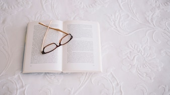 Book with glasses on white cloth