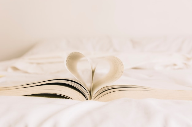 Book with heart lying on bed