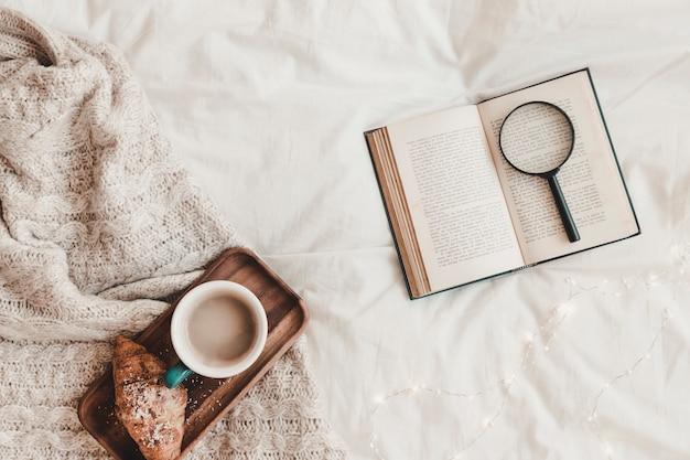 Книга с лупой возле круассана и горячего напитка на подставке, помещенной на плед
