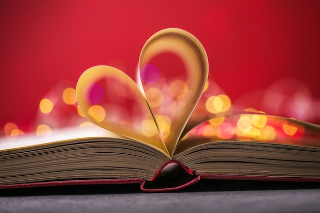 Book with love symbol on red background, heart shape from paper book.