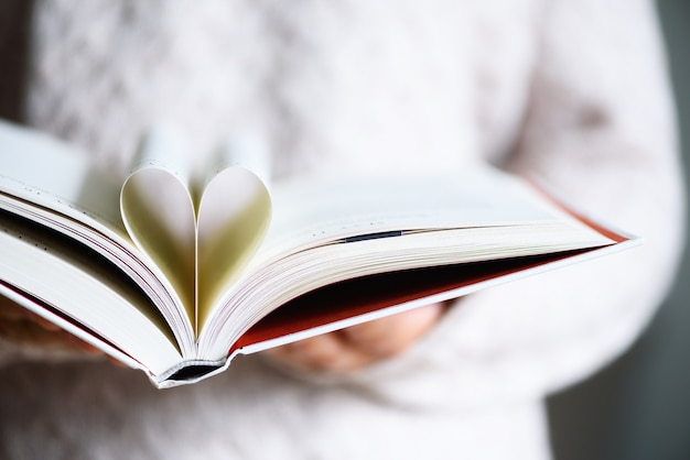 Book with opened pages and shape of heart in girl hands.