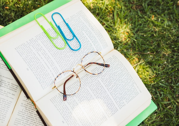 Book with paper clips and glasses on grass