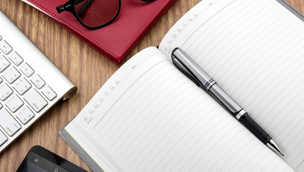 Book with pen, mobile and keyborad on desk