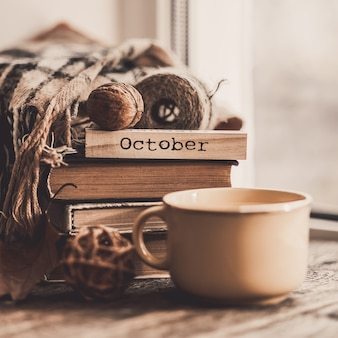 Book with scarf and cup of tea on wood background autumn mood.