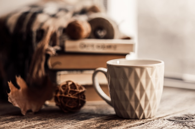 Book with scarf and cup of tea on wood background