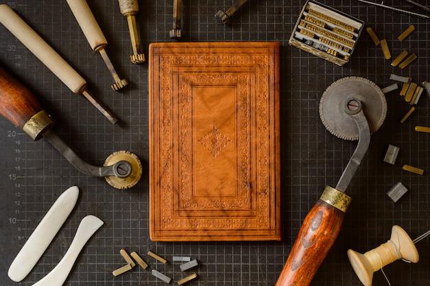제본 도구. 핸드 제본 및 엠보싱 배경 공예를위한 다양한 무역 도구 정물