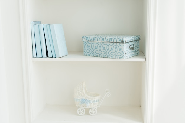 Bookcase with blue books, baby stroller .  white interior. the decor of the room.