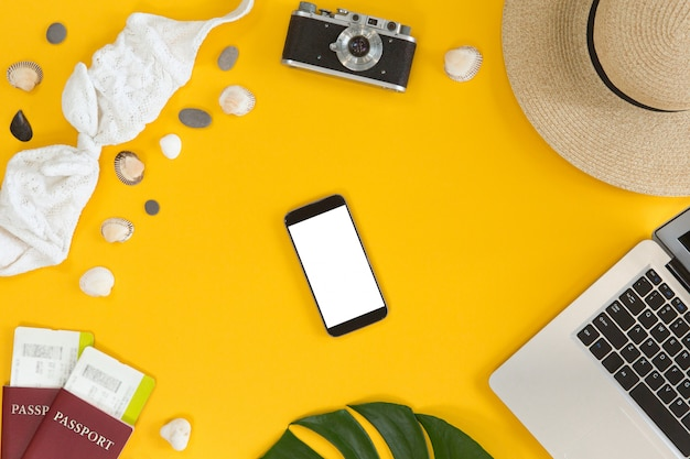 Booking and payment travel online concept, top view, flat lay. mobile phone with white screen near laptop, overhead view of desktop with traveler accessories