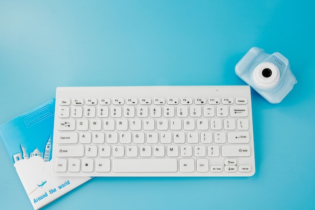 Booking and search flight ticket air international travel concept, keyboard, passport and camera on blue