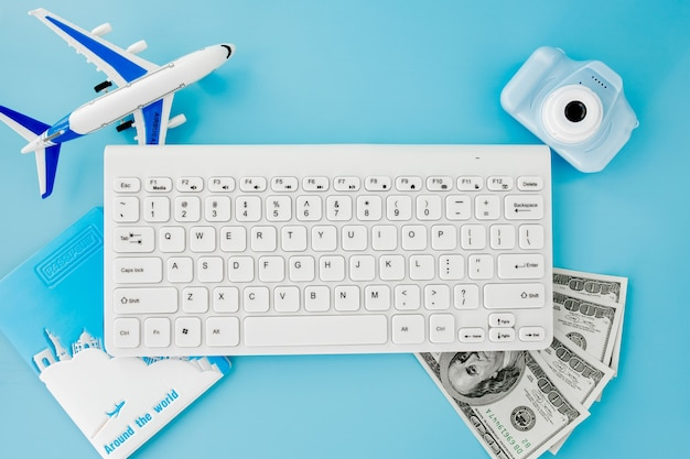 Booking and search flight ticket air international travel concept, keyboard, passport, dollars and airplane on blue background. summer or vacation concept. copy space.