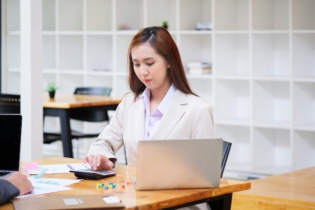 簿記係がオフィスでコンピューターのラップトップ、予算、ローンの紙で電卓を使用しています。企業会計の概念。