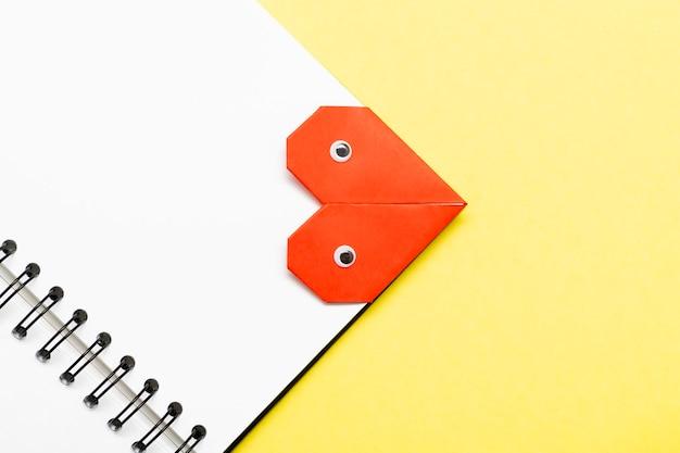 黄色の背景の本のクローズアップの目でハートをブックマークします。