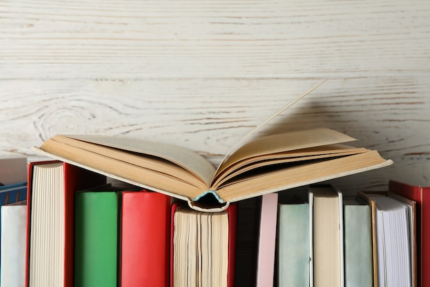 Books against rustic wooden background, space for text