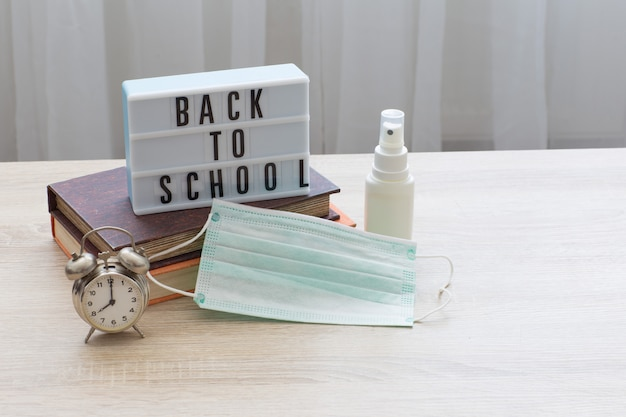 Books, alarm clock, the inscription back to school, a face shield and a hand sanitizer