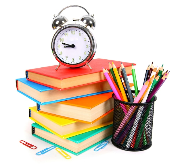 Books, an alarm clock and school tools on white.