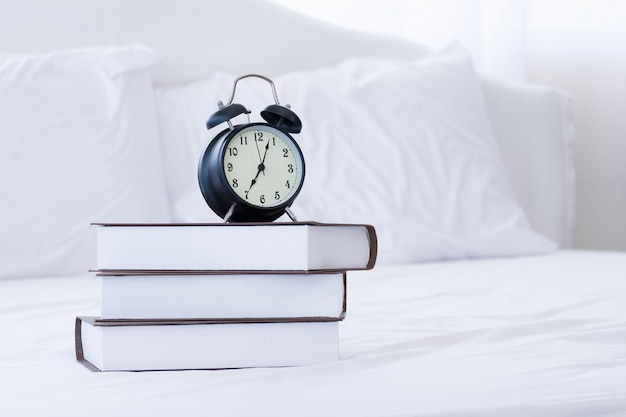 Books and alarm clocks on a white bed.