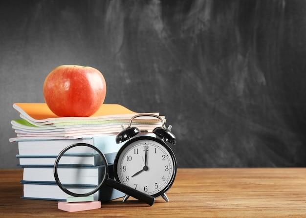 책과 칠판 배경에 알람 시계