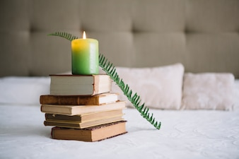 Books and candle on bed