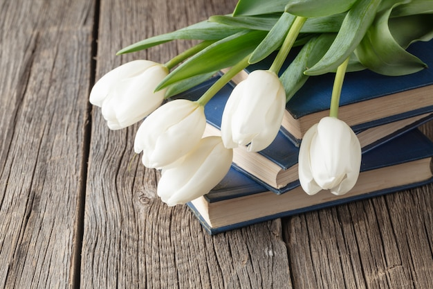 Книги и цветы на деревянном столе