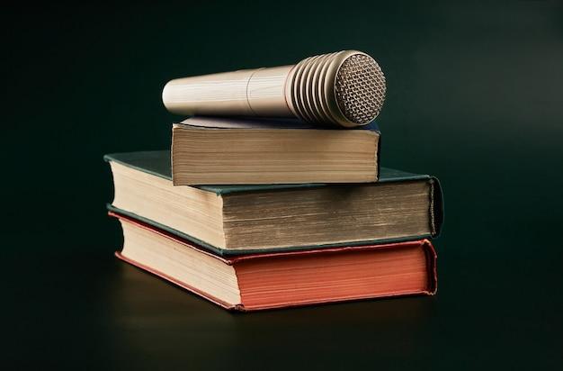 Книги и микрофон на темном фоне.