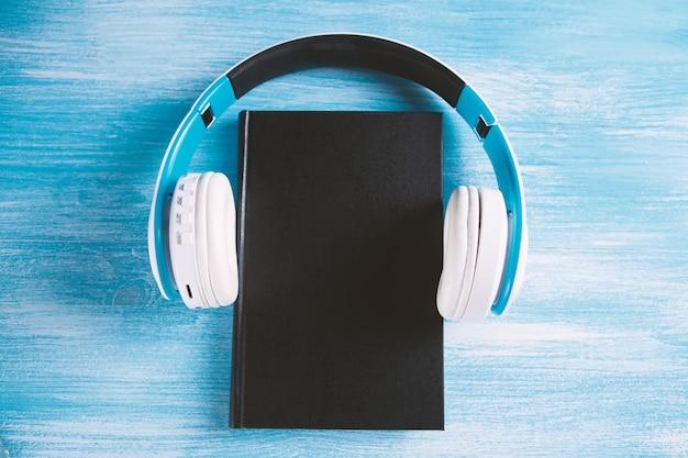 水色の背景、上面図の本とモダンなヘッドフォン。