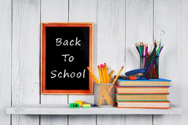 Книги и школьные принадлежности на деревянной полке