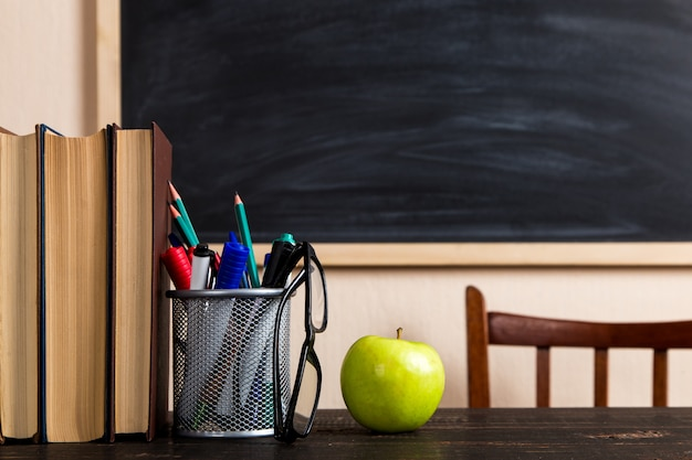 Books, apple, pens, pencils and glasses on a wooden table, against a chalk board.